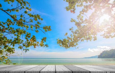 Soft white wooden tabletop with beautiful nature beach and blue sky background use for put your product or something.