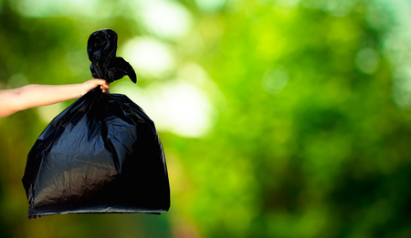 recycle icon: human hand showing garbage bag on fresh green nature blurred background, recycle concept