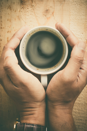 Human hands holding a cup of coffee put on tabletop in the morning vintage tone style