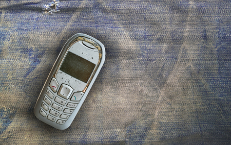 old vintage: vintage mobile phone put on old denim background with blank space for texts display Stock Photo