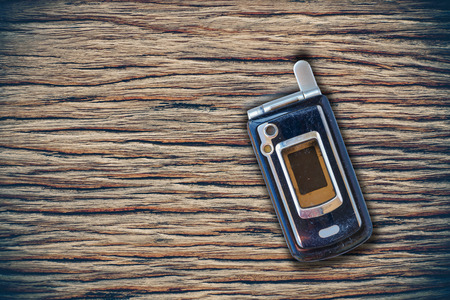 blank space: Vintage mobile phone put on wooden with blank space for texts display