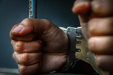 Human hand of prisoner on steel lattice close up.