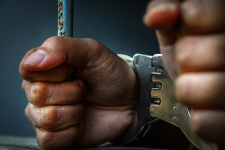 Menselijke hand van gevangene op stalen rooster close-up.