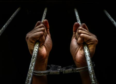 Main humaine de prisonnier sur un treillis en acier proche. Banque d'images - 71647418