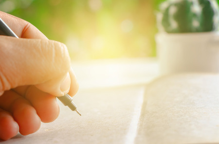 writing paper: Human hand gesture writing something on blank paper with blurred nature background