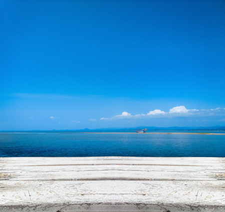 wooden tabletop with blurred of beautiful beach and sea on summer background Stock Photo