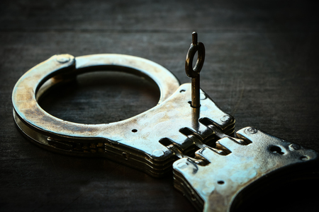 cuff link: Handcuffs on old wooden table background
