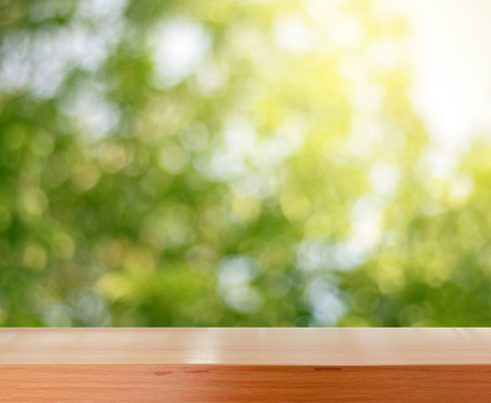 wooden tabletop surface with fresh green nature background