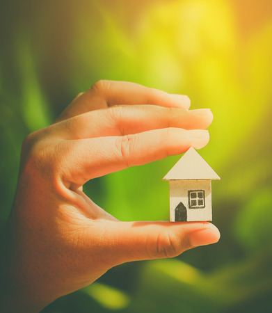 Woman hands holding house model, eco concept
