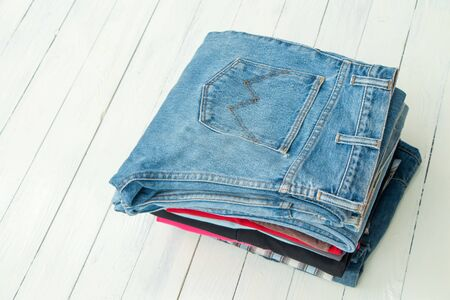denim jeans put on white wooden table Stock Photo
