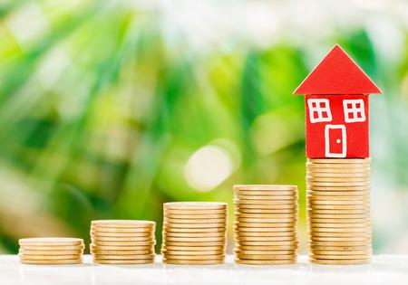 Red Home-Modell auf goldenen Münzen mit frischen grünen Natur Hintergrund, sparen, um Haus-Konzept zu kaufen