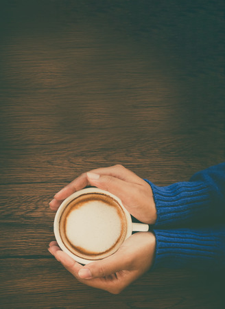 stiring: Young woman hand holding cup of mocca coffee on wooden table background