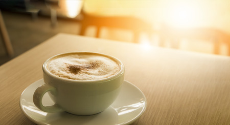 Cup of cappuccino coffee with sun flare put on the table at the shop Stock Photo