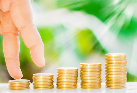 Human finger gesture like walking on the golden coins with fresh green nature blurred background, business concept.
