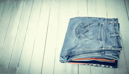 pile of jeans put on a wooden background with space, vintage tone style. Stock Photo