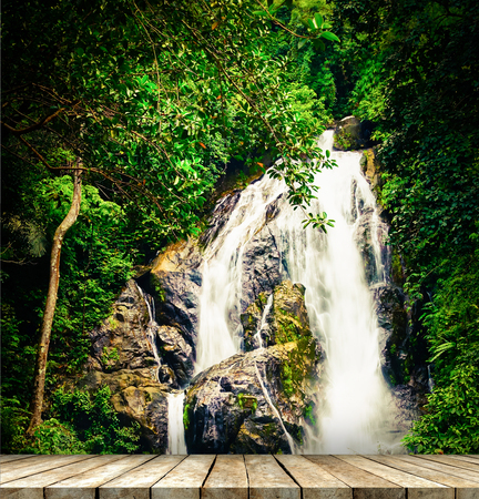 Wooden plank with fresh nature waterfalls background at the forest Stock Photo