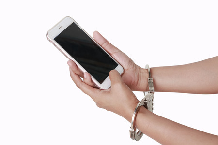 Female hand holding mobile phone with handcuffs. Stock Photo