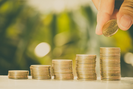 Close up golden coins put on white wooden tabletop with fresh green nature blurred background, saving money concept.