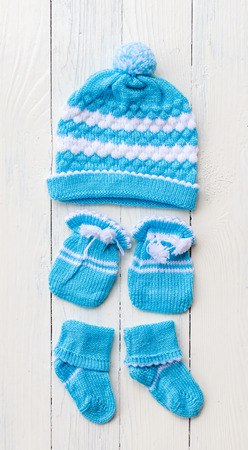 Close up blue baby hand gloves and sock put on white wooden table background
