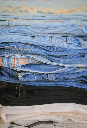 Stack of blue jeans on wooden background with copy space