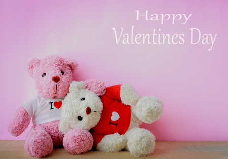 White and pink teddy bear with red heart on red background. Valentines day concept. Stock Photo
