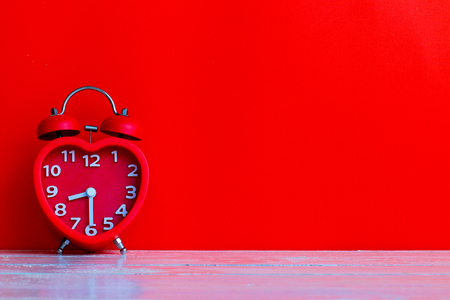 Red clock mark at 8.30 oclock put on white wooden table top in the morning with red background and space use for texts or products display