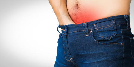 Close up man problem with itching inside trousers jeans isolated on white background Stock Photo