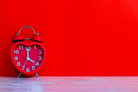 Close up red alarm clock mark at 4 oclock put on red blank space background