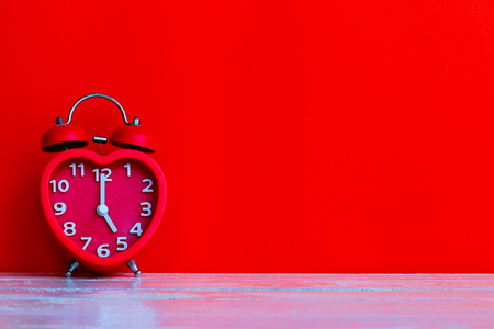 Close up red alarm clock mark at 5 oclock put on red blank space background