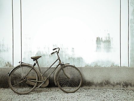 Old bicycle on grunge rustic cement wall background with space