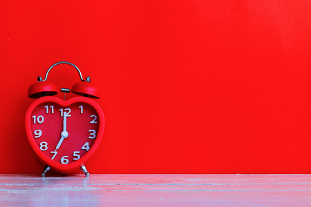 Close up red alarm clock mark at 7.00 oclock on blank space red background