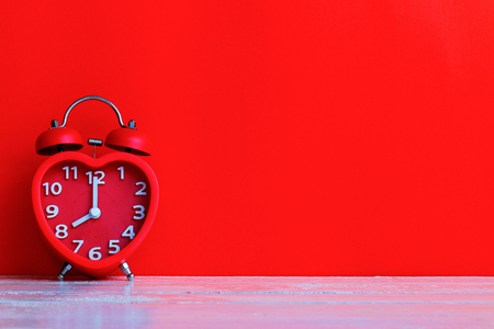 Close up red alarm clock mark at 8.00 oclock with red space background put on wooden table top