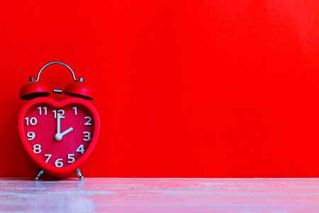 Close up red alarm clock mark at 14.00 o'clock with red space background put on wooden table top Imagens - 100530487