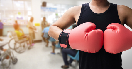 human with glove punch with blurred hospital background, Sick fighting concept. 版權商用圖片