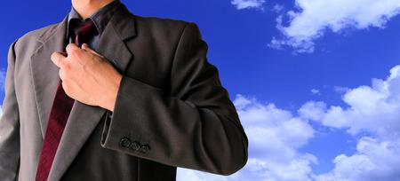 Hombre de negocios en traje listo para luchar con el cielo azul y el edificio borroso