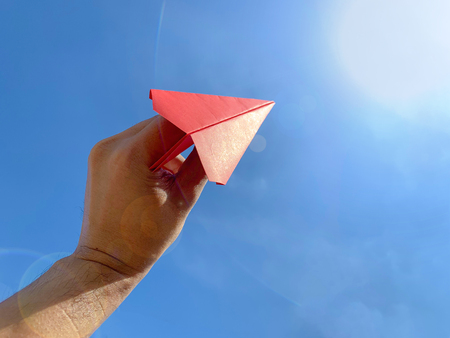 Close up human holding red paper airplane with clear blue sky background and sun flare