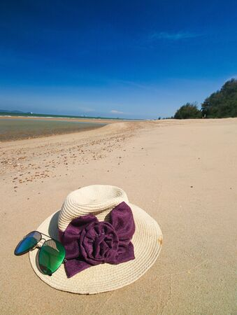 Close up hat and glasses put on the sand at the beach phuket the land with blue sky background for relax Reklamní fotografie - 132133900