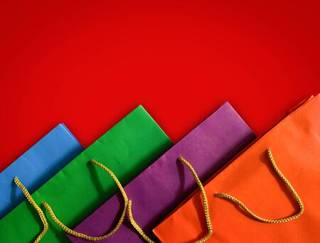 Close up top view of colorful paper shopping bag on red background