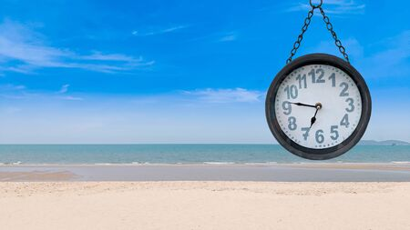 Classic clock mark at the morning with peaceful beach and sky, Recreation times concept. Reklamní fotografie - 132133888