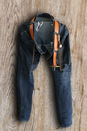 Close up old denim jeans trouser with leather belt put on wooden background Reklamní fotografie - 132133992