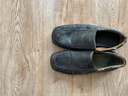 Close up retro old vintage leather shoe put on wooden table top Stock Photo