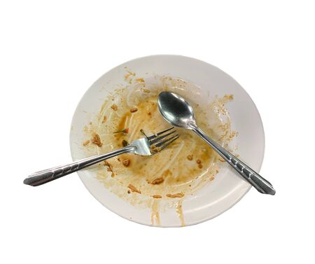 Close up dirty empty dish with spoon and fork put on table Standard-Bild