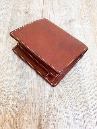 Close up brown leather luxury wallet put on wooden table background