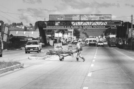 third wheel: Man pushes whee barrow with bundle of wood across a busy road or highway in La Aldea El Caman, Patzicia, Guatemala.