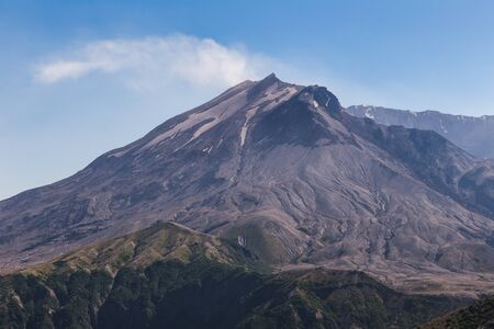 Mount St. Helens with Smoke Billowing. Sunny summer day under blue sky.