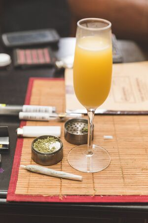 Alcoholic beverage in focus, on table place mat near cannibus and related accessories. Stock Photo