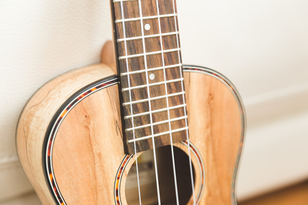 New, upscale ukulele with four strings and unique, textured wood grain finish.