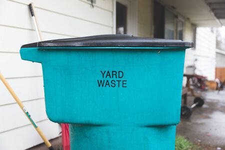 Blue and black plastic container for yard waste in home back yard.