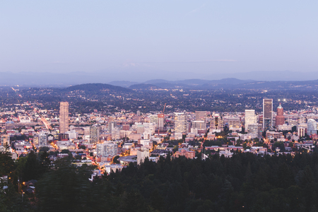 northwest: Wide city view of Portland, Oregon with Mount Hood in the background. Hazy summer or fall evening setting.