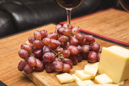 Ripe red grapes near sliced white cheese and a wine glass.